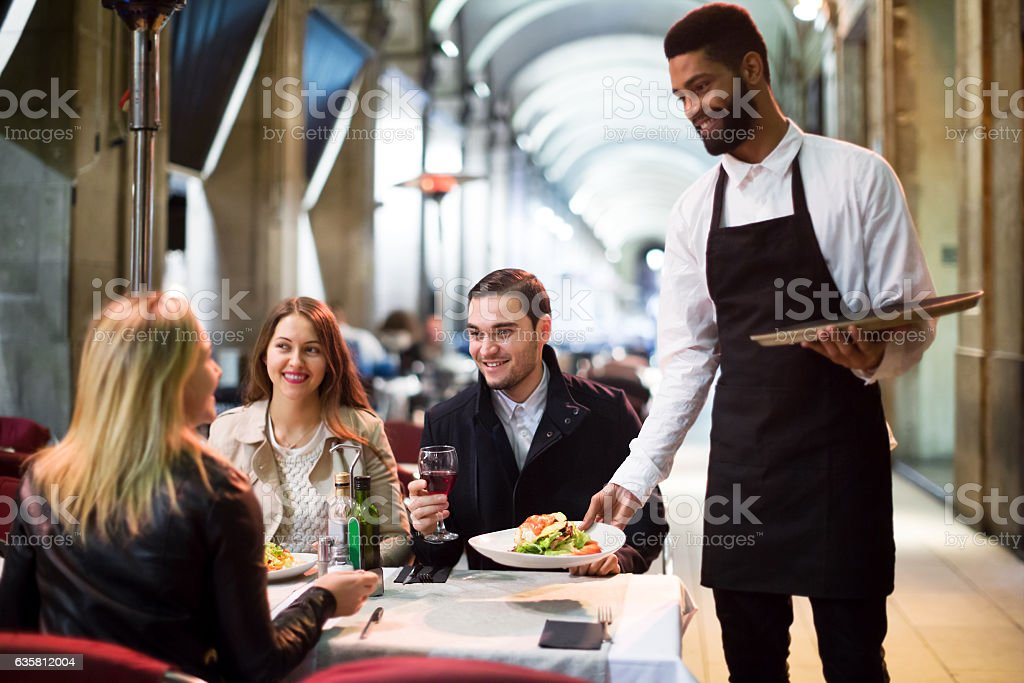Black waiter serving table on the terrace stock photo