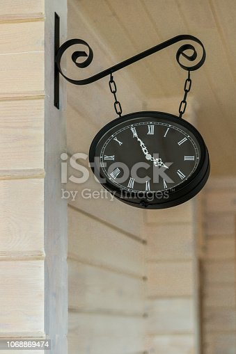 671883446 istock photo Black wall clock on a chain on the wall of a wooden house 1068869474