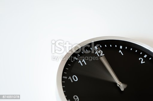 istock Black wall clock with hand in motion 874551078