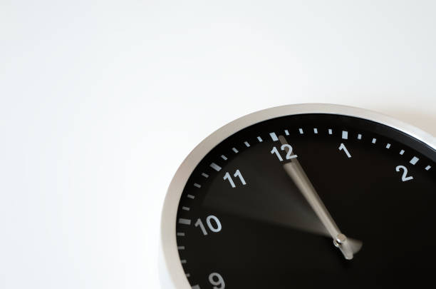 Black wall clock with hand in motion stock photo