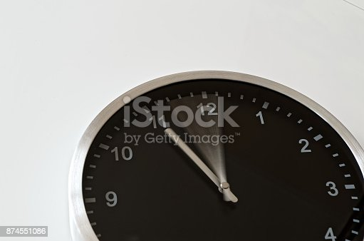 istock Black wall clock with hand in motion 874551086