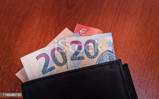 1170746979istockphoto black wallet with euro banknotes 1165085732