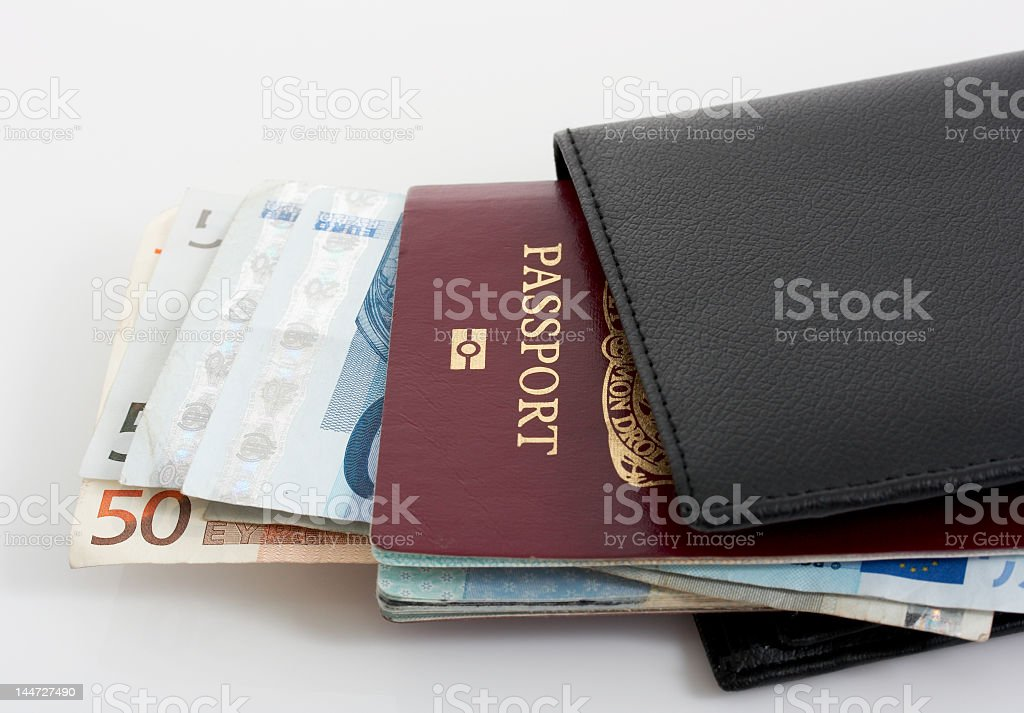 A black wallet with passport and paper bills stock photo