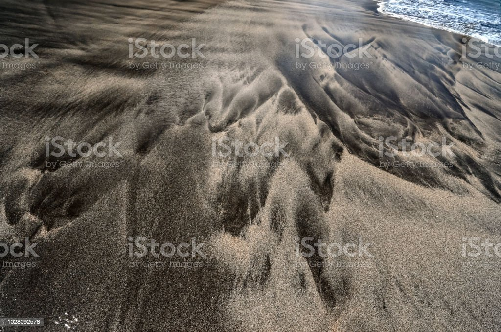 Black wet volcanic sand beach pattern stock photo