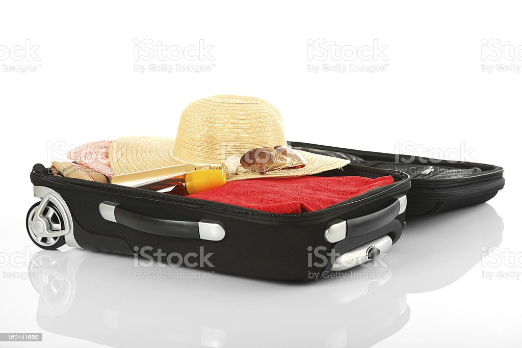 Black wheeled suitcase filled with summer clothes and hat stock photo