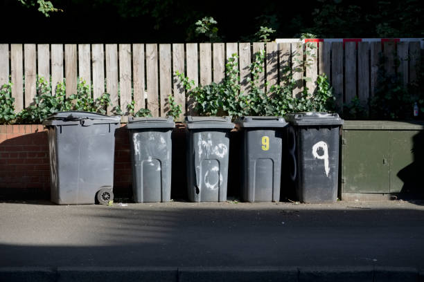 Black wheelie bins in a row on street with house numbers printed on front waiting for bin men to collect stock photo