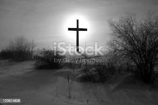 Backlit black and white cross on a snow covered field with shadow