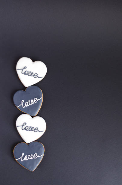 Black, white hearts lie alternately on a black vertical background.  Selective focus, copy space. Black, white hearts lie alternately on a black vertical background.  Selective focus, copy space. alternately stock pictures, royalty-free photos & images