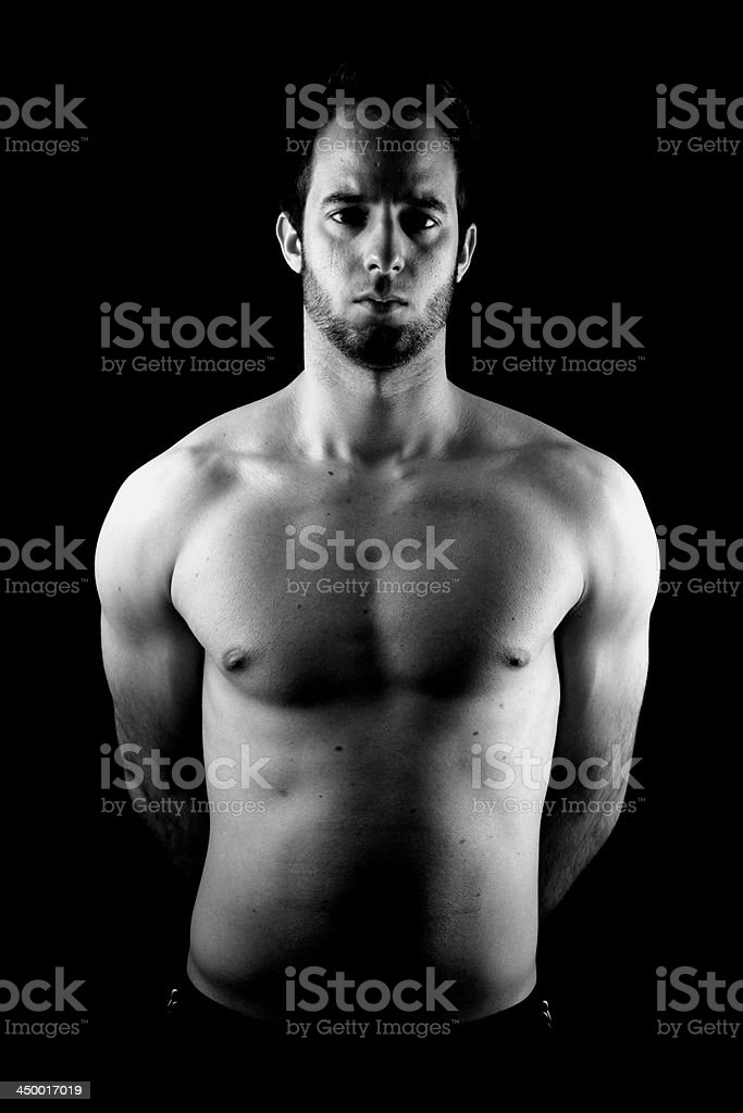 black & white low-key studio shot of musculous man stock photo