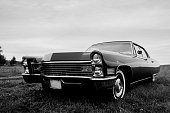 Parked in a field at sunset this old Fleetwood Cadillac 1967 car is pimped up to drive and look like new.  View of the front grill in black and white to showcase the 'serious' side of this classic car.
