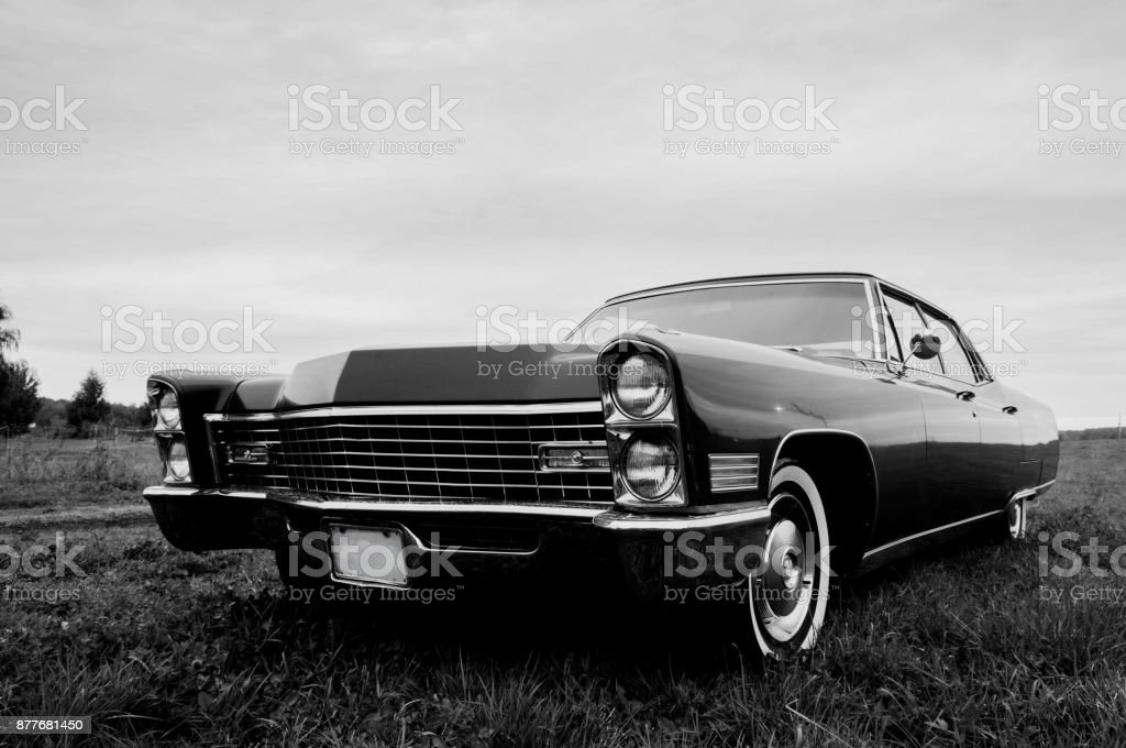 Black & White photo of an old 1967 car parked in a field stock photo