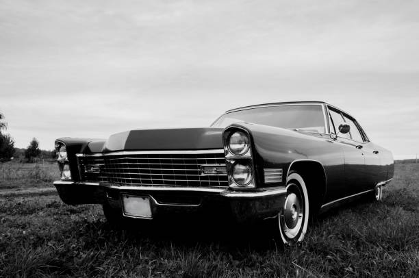 Black & White photo of an old 1967 car parked in a field Parked in a field at sunset this old Fleetwood Cadillac 1967 car is pimped up to drive and look like new.  View of the front grill in black and white to showcase the 'serious' side of this classic car. 20th century history stock pictures, royalty-free photos & images