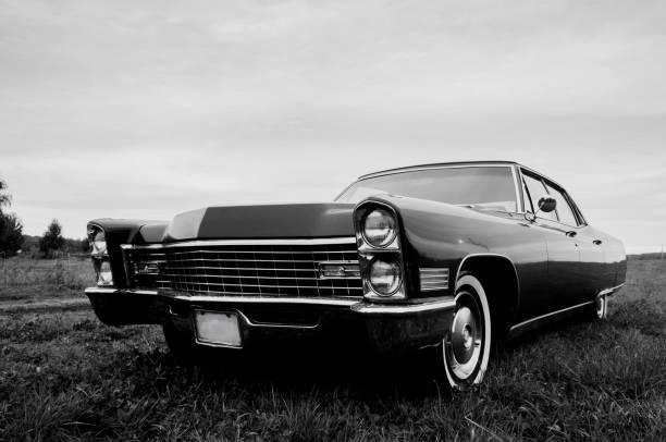 & schwarz-weiß-foto eines alten 1967 autos geparkt in einem feld - oldtimer veranstaltungen stock-fotos und bilder