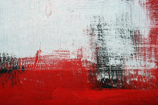 Stroke of brush with black,white and red acrylic paint on dusty rough metal surface. Textured abstract multicolor grunge background. Street graffiti close up