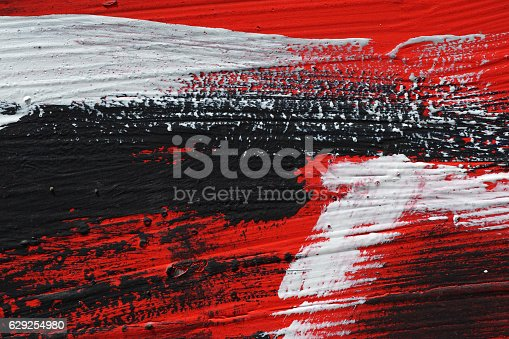 629255068 istock photo Black, white, red acrylic paint on metal surface. Brushstroke 6 629254980