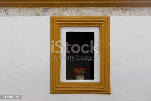 Black Window Exterior with Red Roses Vase Detail and Rectangular Frame on a White Wall House Background in Residential District Street of old City Antigua, Guatemala