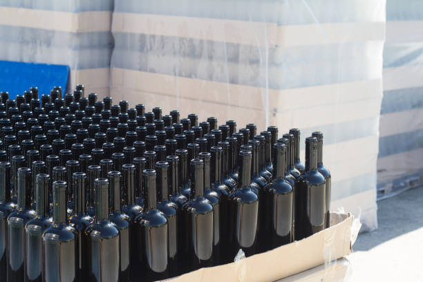 black wine bottles on pallets in outside storage area stock photo