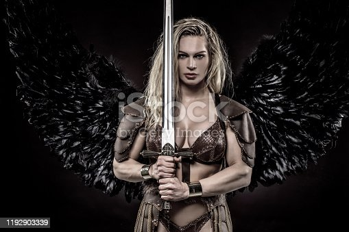 Black Wing Viking Valkyrie young blond female wielding a sword in a studio shot