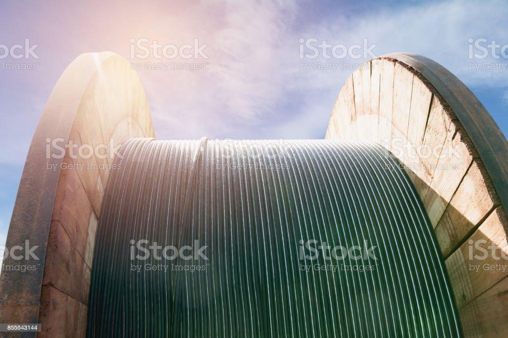 cable eléctrico de alambre negro con bobina de cable eléctrico bajo el cielo de madera. - foto de stock