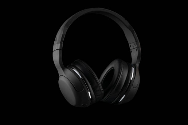 Black wireless headphones isolated on a black background. Black wireless headphones isolated on a black background. wireless headphones stock pictures, royalty-free photos & images