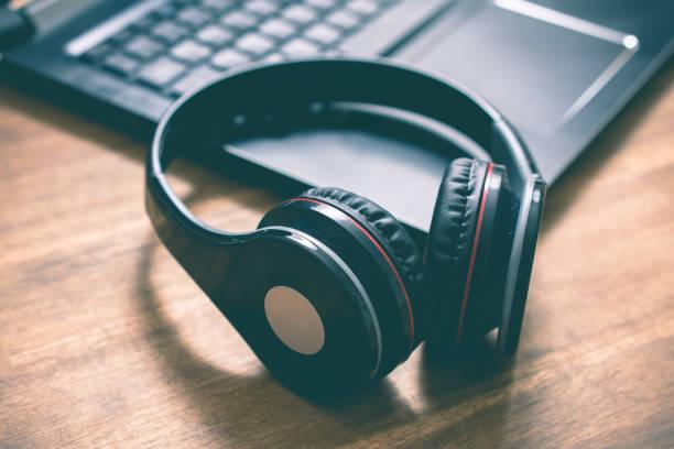 schwarzen overhead funkkopfhörer liegen an der ecke einer laptop-tastatur in einem büro - geräusche app stock-fotos und bilder