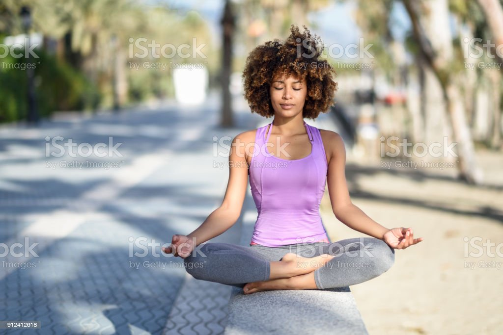 Black woman, afro hairstyle, in lotus asana with eyes closed in the beach stock photo