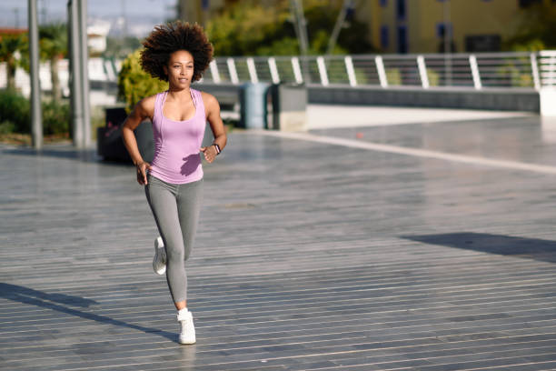 Black woman, afro hairstyle, running outdoors in urban road. stock photo