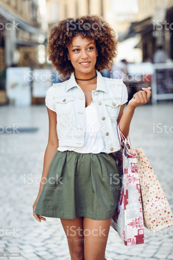 Young black woman, afro hairstyle, with shopping bags in the street....
