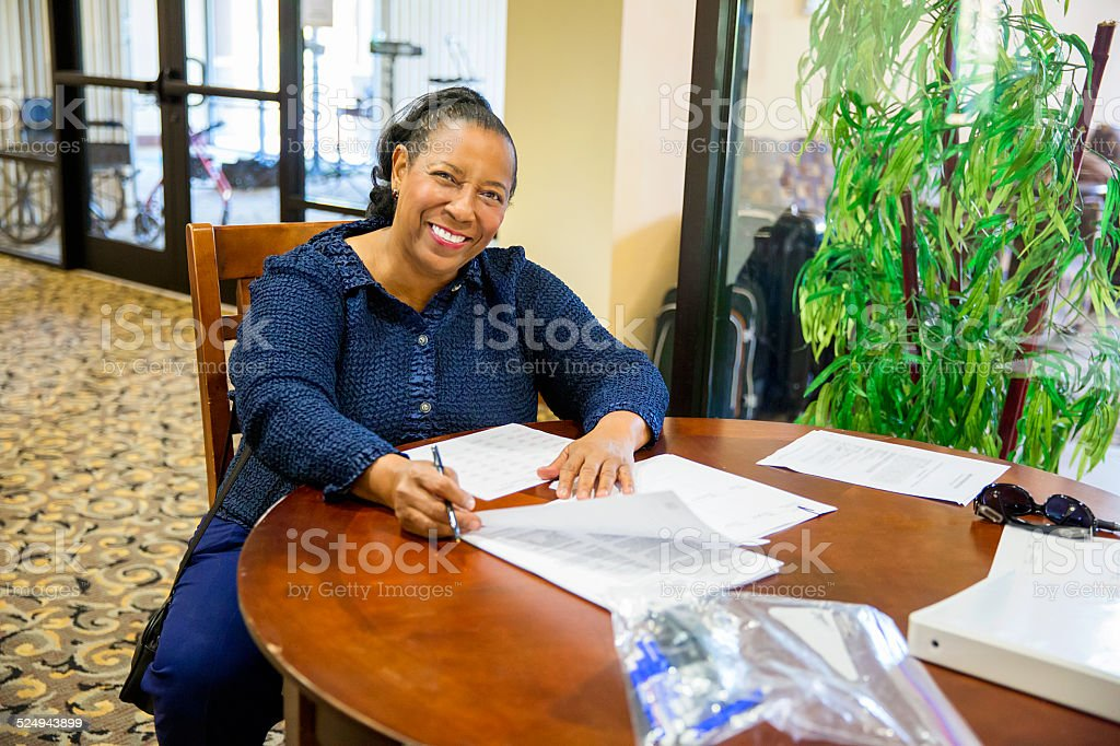 Black woman at a table smiling while filling out forms stock photo