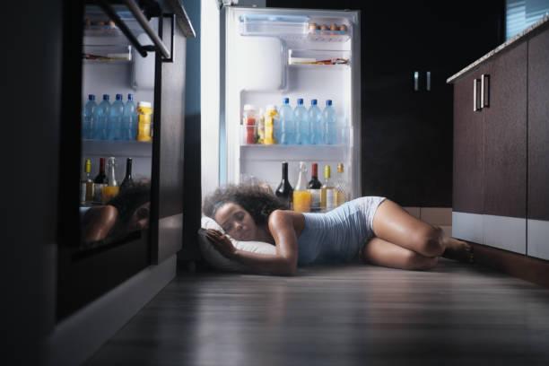 svart kvinna vaken för heat wave sover i kylskåp - feber bildbanksfoton och bilder