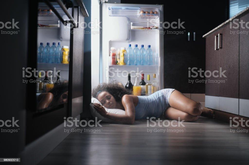 Black Woman Awake For Heat Wave Sleeping in Fridge stock photo