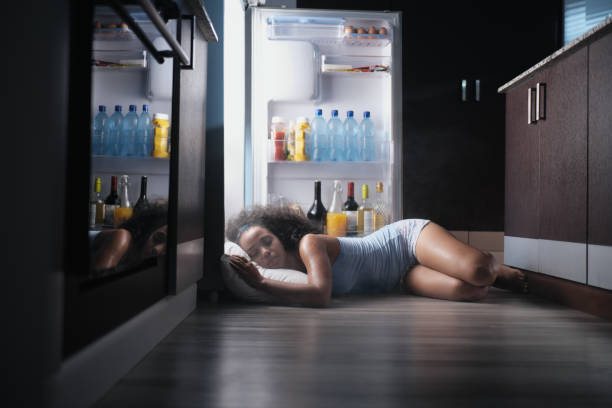 black woman awake for heat wave sleeping in fridge - ogień zdjęcia i obrazy z banku zdjęć