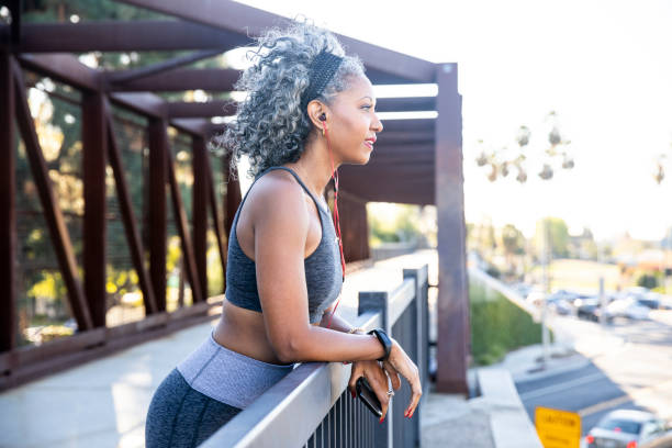 A Black Woman checking her smartwatch during her workout Beautiful black woman working out in the city fitness tracker stock pictures, royalty-free photos & images