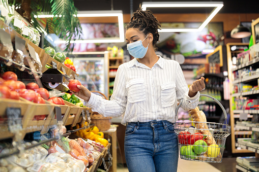 Grocery Shopping. Black Woman Choosing Fresh Vegetables In Supermarket, Walking With Basket Full Of Food Along Shelves In Store Aisle. Groceries Shop Sales And Discounts Concept