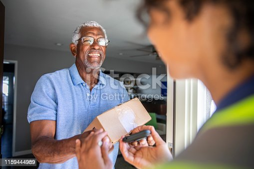 A young black woman delivers a package to a senior black man