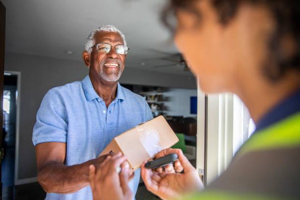 black woman delivers package to customer - источник стоковые фото и изображения