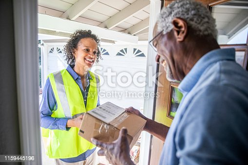 istock Black Woman Delivers package to customer 1159445196