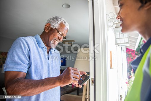 istock Black Woman Delivers package to customer 1159445240