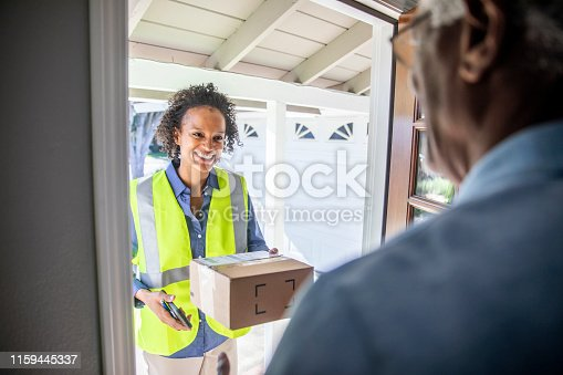 istock Black Woman Delivers package to customer 1159445337