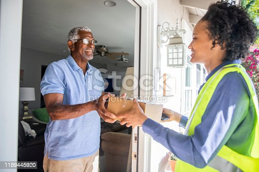 istock Black Woman Delivers package to customer 1159445920
