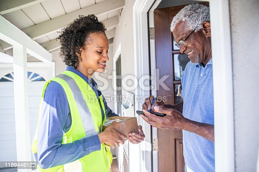 istock Black Woman Delivers package to customer 1159446122