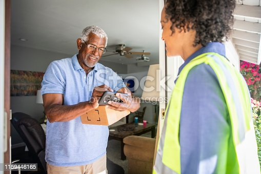 istock Black Woman Delivers package to customer 1159446165