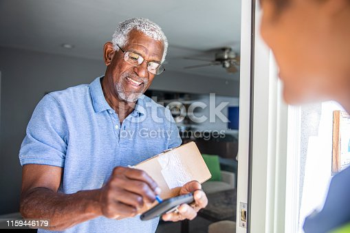 istock Black Woman Delivers package to customer 1159446179