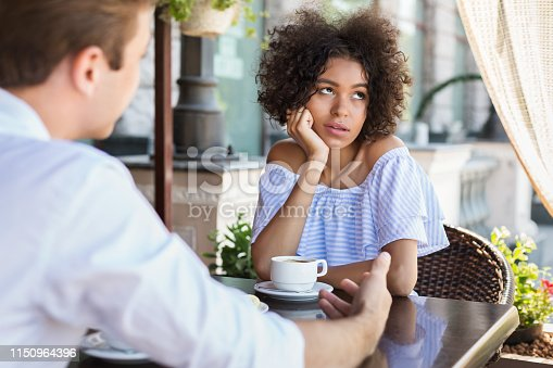 Black woman disinterested with blind date at outdoor cafe