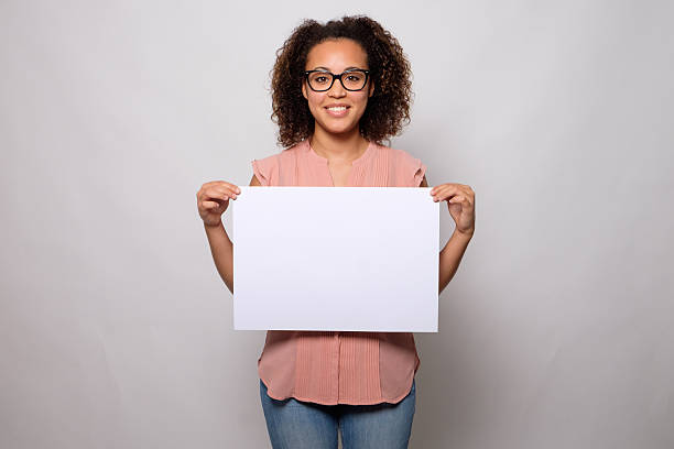 Black woman displaying white banner stock photo