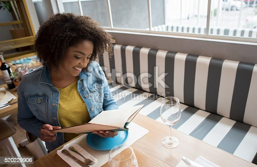 Happy black woman eating at a restaurant and taking a look at the menu while she waits