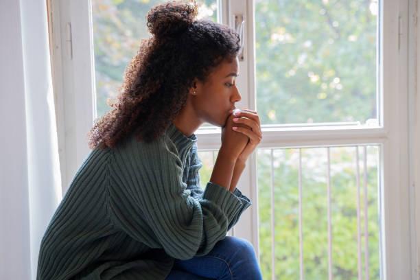 Black woman feeling depression symptoms alone at home stock photo