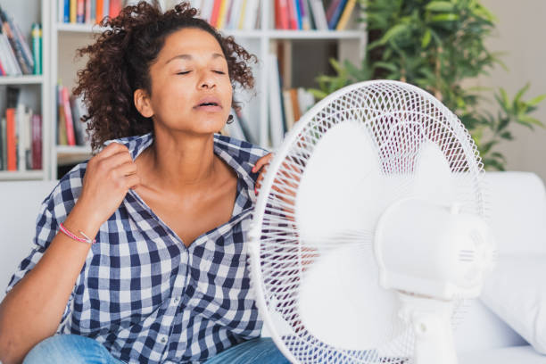 Black woman feeling hot and trying to refresh stock photo