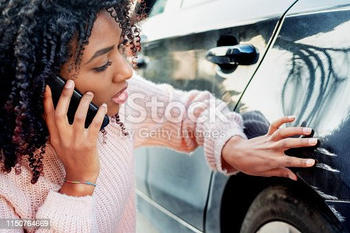 istock Black woman feeling sad after scratching her auto 1150764669