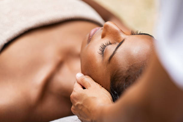 Black woman getting head massage Beautiful african woman getting face massage in beauty spa. Black girl with closed eyes relaxing in outdoor spa while getting head massage. Serene woman relaxing outdoor in a beauty center. massage stock pictures, royalty-free photos & images